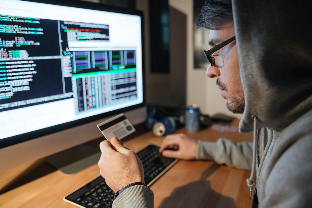 Concentrated young hacker in glasses stealing money from different credit cards sitting in dark room-2