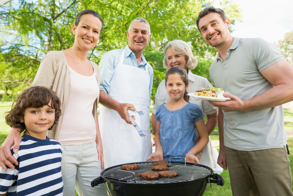 Portrait of an extended family standing at barbecuing in the park