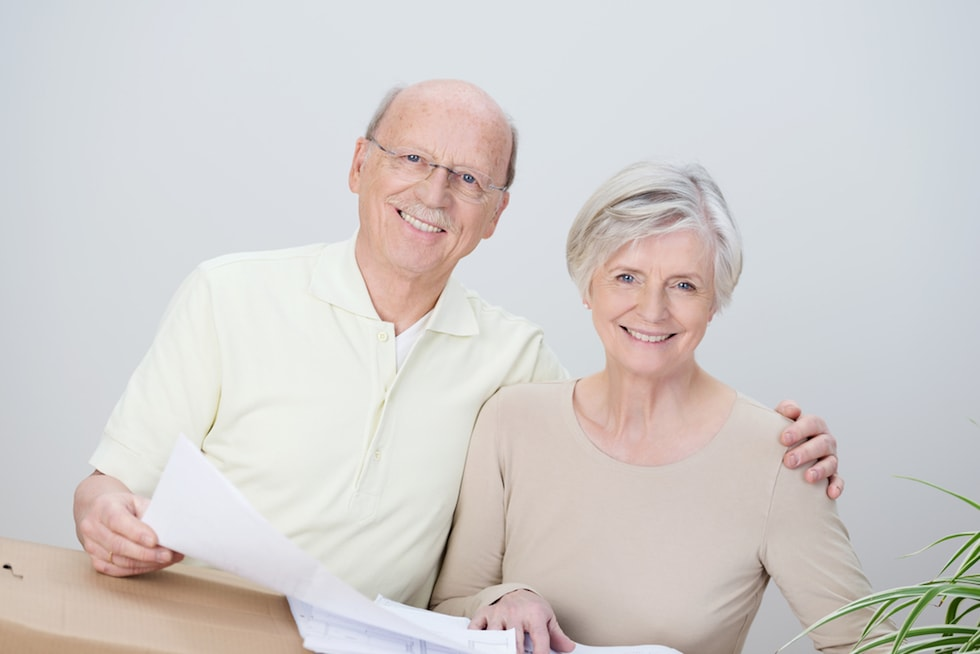Smiling affectionate senior couple standing with the husbands arm around his wife looking at documents resting on a brown cardboard carton as they plan their move to a new home-2