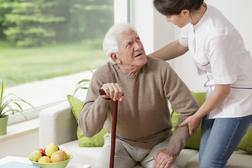 Young woman helping old man to stand up